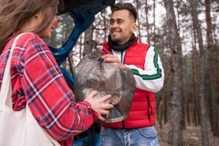 Junge Frau mit Sonnenbrille und glücklicher Mann mit Müllsack im Wald
