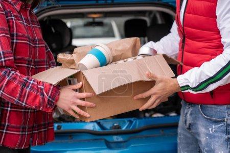 Photo pour Vue recadrée de jeune homme et femme tenant boîte en carton avec tasse réutilisable - image libre de droit