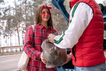 Glückliche junge Frau mit Sonnenbrille und Mann mit Müllsack neben Auto im Wald