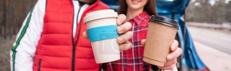 cropped view of man and woman holding reusable and paper cups, banner