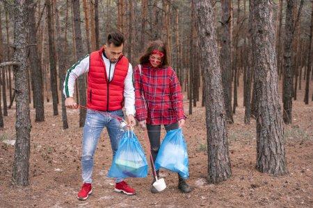 junges Paar mit Müllsäcken sammelt Müll mit Greifwerkzeug im Wald auf