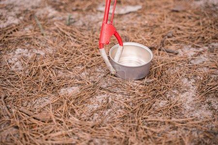 Werkzeug in der Nähe von Aluminiumbehältern auf dem Boden im Wald aufheben