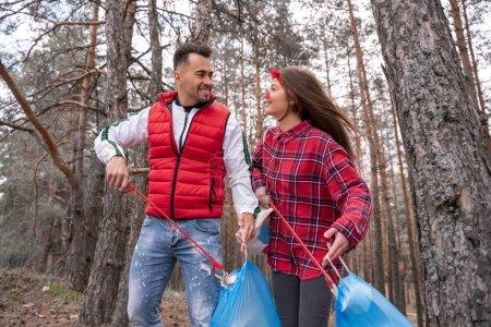 Photo pour Couple heureux avec des sacs poubelle ramasser les ordures avec des outils de préhension dans la forêt - image libre de droit