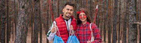Photo pour Couple heureux avec des sacs poubelle tenant des outils de ramassage dans la forêt, bannière - image libre de droit