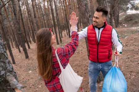 Photo for Happy man with trash bag giving high five to woman while looking at each other in forest - Royalty Free Image