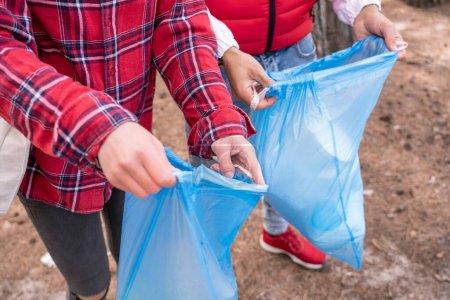 vue partielle de l'homme et de la femme tenant des sacs poubelles bleus