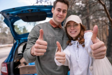 Photo for Happy couple showing thumbs up near car on blurred background - Royalty Free Image