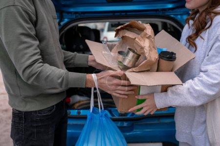 Ausgeschnittene Ansicht von Freiwilligen, die Müll in Karton in der Nähe von Auto halten