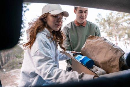 Photo pour Jeunes bénévoles tenant boîte en carton avec des déchets près de la voiture - image libre de droit