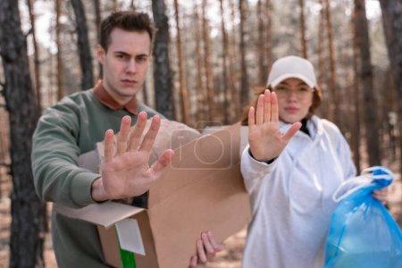 Photo pour Jeunes bénévoles tenant boîte en carton et sac poubelle avec des déchets tout en montrant geste d'arrêt - image libre de droit
