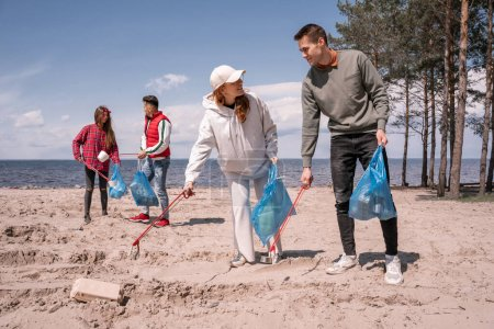 Photo for Happy group of volunteers with trash bags picking up rubbish with grabber tools - Royalty Free Image
