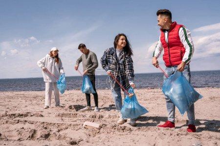 Photo pour Groupe joyeux de bénévoles avec des sacs poubelle ramasser les ordures avec des outils de préhension - image libre de droit