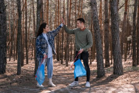 full length of happy couple with trash bags giving high five while picking up rubbish with grabber tools in forest