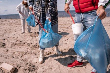 Photo pour Bénévoles ramassant les ordures dans des sacs poubelle - image libre de droit