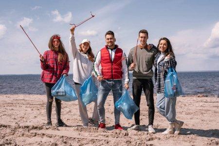 Photo pour Groupe de bénévoles heureux tenant des outils de ramassage et des sacs poubelle - image libre de droit