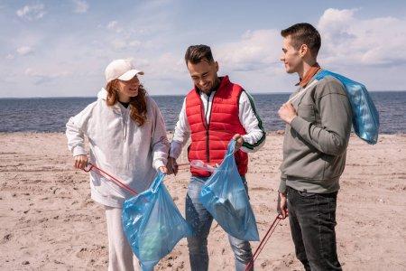 Photo pour Groupe d'hommes et de femmes heureux ramasser les ordures dans des sacs poubelle - image libre de droit