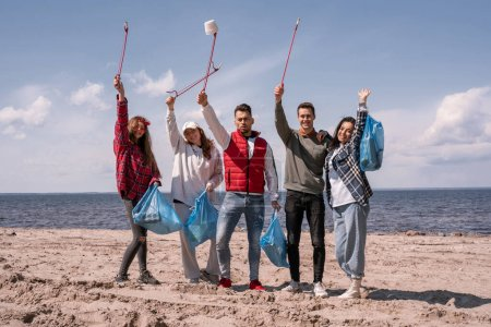 Photo for Group of cheerful volunteers holding pick up tools and trash bags - Royalty Free Image