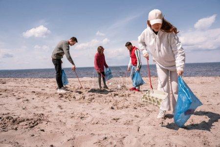 Gruppe von Freiwilligen mit Müllsäcken, die Müll im Sand aufsammeln