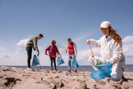 Photo pour Femme heureuse tenant sac poubelle et ramassant des ordures sur le sable près du groupe de bénévoles - image libre de droit