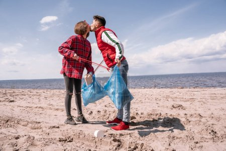 Photo for Couple with trash bags and grabbers kissing while standing on sand - Royalty Free Image