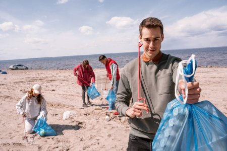 Photo for Happy man holding trash bag near group of blurred volunteers picking up rubbish on sand - Royalty Free Image