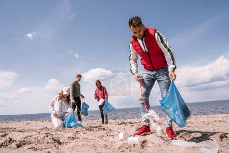 Junger Mann hält Müllsack in der Hand und sammelt Müll auf Sand in der Nähe von Freiwilligen