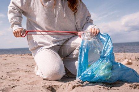 Photo pour Vue recadrée d'une femme tenant un sac poubelle et ramassant des ordures sur du sable - image libre de droit