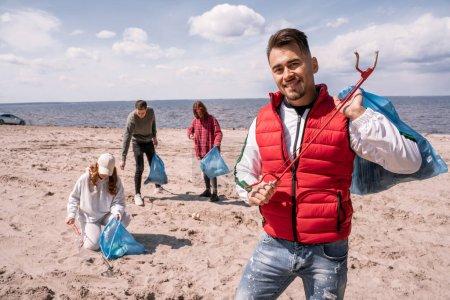 Photo pour Homme joyeux tenant sac poubelle et saisir près de bénévoles flous collecte des ordures sur le sable - image libre de droit