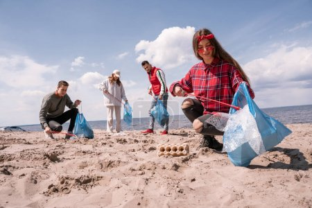 smiling young woman holding trash bag and collecting rubbish with grabber on sand near group of volunteers