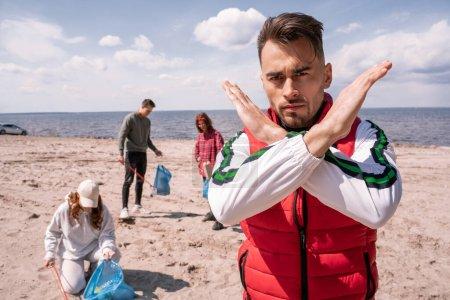 Photo pour Homme montrant geste d'arrêt près du groupe de bénévoles ramasser des ordures, concept d'écologie - image libre de droit