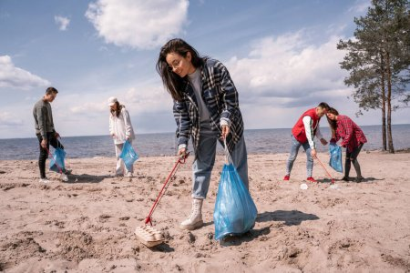 Photo for Smiling young woman holding trash bag and collecting rubbish on sand near group of volunteers - Royalty Free Image