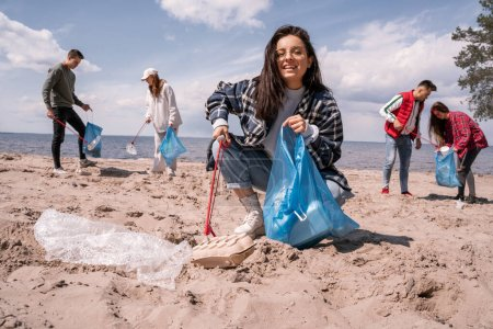 Glückliche junge Frau sammelt mit Greifer Müll in der Nähe einer Gruppe Freiwilliger