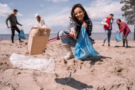 Photo pour Jeune femme floue ramassant des ordures avec grabber près du groupe de bénévoles - image libre de droit