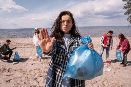 Photo pour Jeune femme montrant un geste d'arrêt près du groupe flou de bénévoles ramasser des ordures, concept d'écologie - image libre de droit