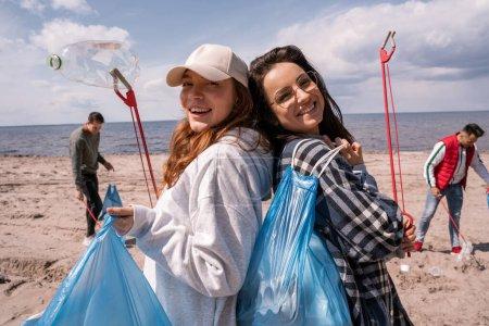 Photo pour Jeunes femmes heureuses avec des saisies et des sacs poubelles à l'extérieur - image libre de droit