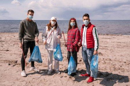 Photo pour Jeunes femmes et les hommes dans des masques médicaux tenant des sacs poubelle et attrape à l'extérieur, ramasser concept de poubelle - image libre de droit