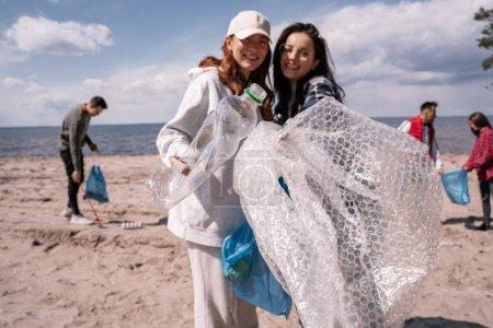 Photo pour Jeunes femmes heureuses ramassant des déchets en plastique à l'extérieur - image libre de droit