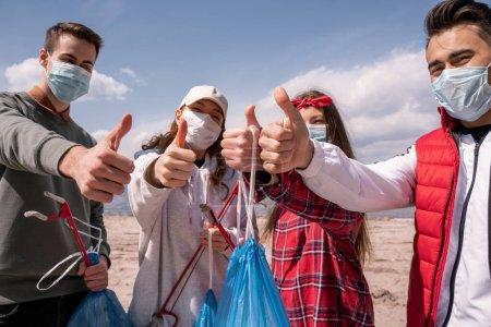 Photo pour Jeunes volontaires dans des masques médicaux tenant sacs poubelles et attrapeurs tout en montrant les pouces vers le haut, ramasser concept poubelle - image libre de droit