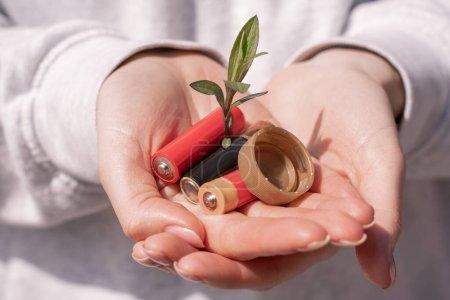 vista recortada de la mujer sosteniendo baterías, tapa de botella de plástico y planta verde en las manos