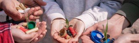 Photo pour Vue recadrée de bénévoles tenant des piles, des bouchons de bouteille en plastique et des plantes vertes dans les mains, bannière - image libre de droit