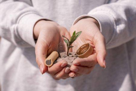 Photo pour Vue recadrée de la femme tenant la batterie, capuchon en plastique et plante verte dans les mains - image libre de droit