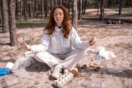 Photo for Young woman with closed eyes meditating near trash on ground - Royalty Free Image
