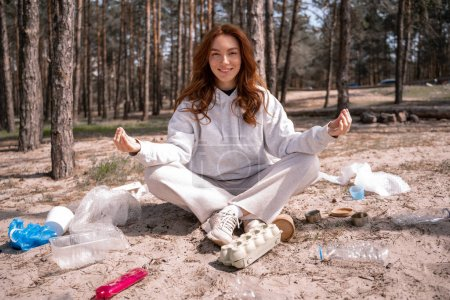 Photo for Happy young woman with crossed legs sitting and meditating near trash on ground - Royalty Free Image