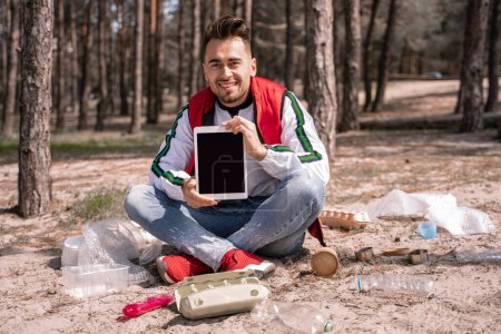 Photo for Happy man with crossed legs sitting and holding digital tablet with blank screen near trash on ground - Royalty Free Image