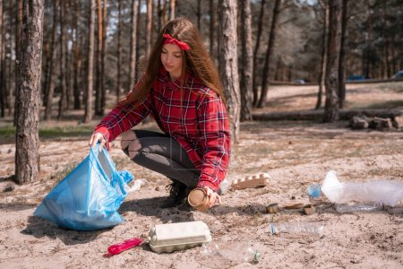 Photo for Young woman holding trash bag and collecting rubbish on ground in forest - Royalty Free Image