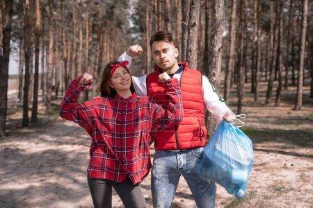 Photo pour Jeune femme montrant geste de puissance et debout près de l'homme tenant sac poubelle - image libre de droit