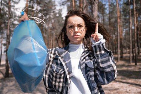 mujer joven advirtiendo mientras señala con el dedo y sosteniendo la bolsa de basura azul en el bosque