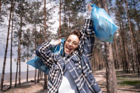 excitée jeune femme dans des lunettes tenant des sacs poubelles bleus dans la forêt