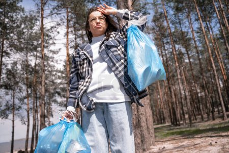 Photo for Displeased young woman in glasses holding blue trash bags in forest - Royalty Free Image