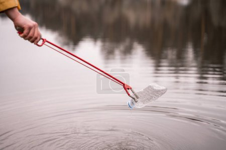 Photo for Cropped view of man holding grabber while picking up plastic bottle from lake - Royalty Free Image